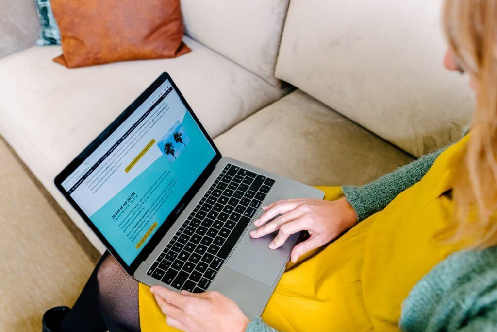 Vrouw die website op laptop bekijkt