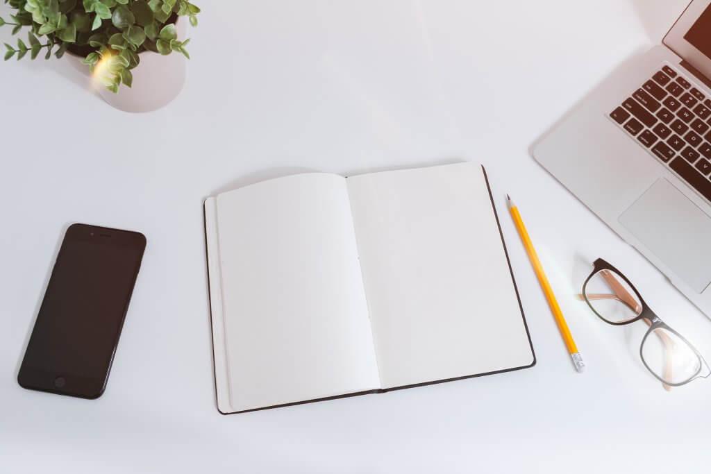 Notitieboek op witte tafel voor onderzoek naar long tail zoekwoorden