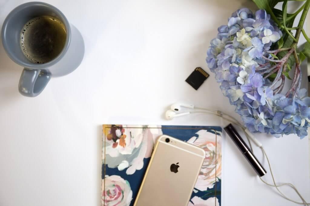 Telefoon met koffiemok en bloemen